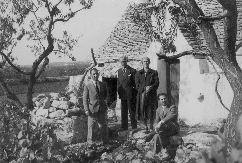 Franco, his parents and brother in front of a trullo, a typical Apulian stone dwelling.