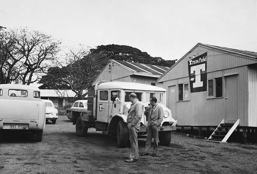 1956. Giancarlo Cecchini inspects a vehicle at the Port Kembla Hostel.