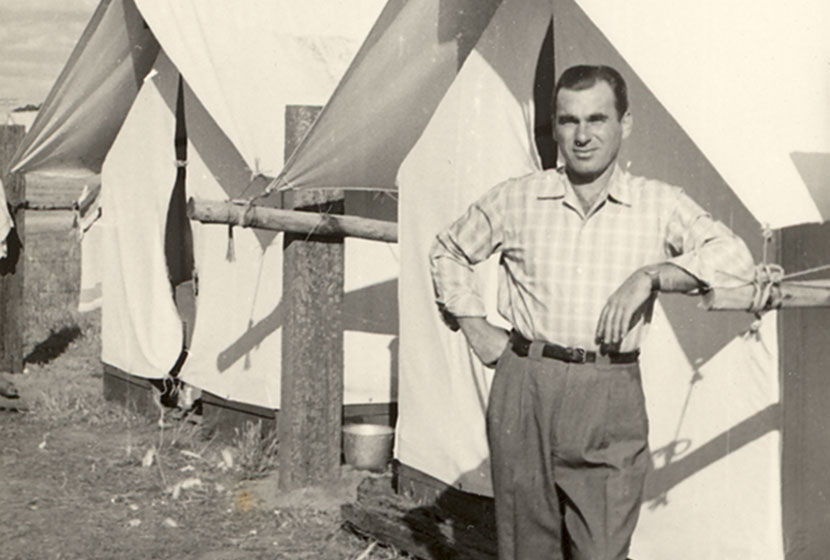 1956. An Italian migrant in his best attire in front of his camp tent in Western Australia.