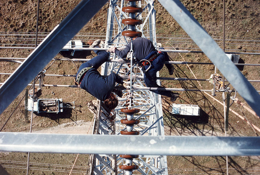 Riggers installing insulator chains on top of a tower.